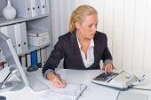 stock photo of depreciation  - an accountant at work in the office with calculator - JPG