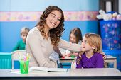Portrait of beautiful kindergarten teacher with little girl sitting at desk in classroom