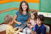 Portrait of young teacher playing xylophone with students in preschool