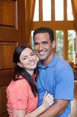 pic of entryway  - Caucasian wife and hispanic husband standing in entryway of home with tall wooden door and windows high ceilings smiling during day - JPG