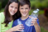 Boy And Girl Holding Clear Bottle For Recycling