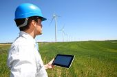 stock photo of turbines  - Businessman checking on wind turbine energy production - JPG