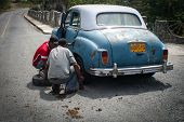 Young Men Changing Tyre In Siboney, Cuba