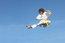 picture of karate-do  - fit child or kid doing martial arts karate kick midair - JPG