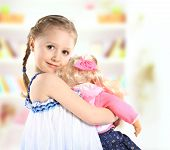 stock photo of baby doll  - cute little girl with a doll on background - JPG