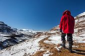 picture of hider  - Hider unidentified  in red jacket black gum boots stands overlooking high mountain valley pass with dirt road for 4x4 vehicles on a blue sky morning - JPG