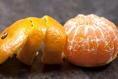stock photo of satsuma  - A spiral peeled Satsuma on a food preparation work surface - JPG