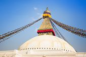 Bodhnath Stupa with buddha eyes and prayer flags, clear blue sky, Kathmandu, Nepal. Stock Photo: