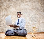stock photo of om  - Happy Indian businessman doing yoga and typing on his laptop with om statue near by in the office at brown background - JPG