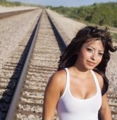 Woman walking along rail road track line