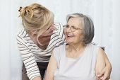 picture of only mature adults  - Mature woman embracing her senior mother at home - JPG