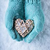 Female hands in light teal knitted mittens with entwined beige flaxen heart on a white snow backgrou
