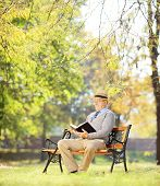 Senior man with hat sitting on a wooden bench and reading a novel, in a park, shot with a tilt and s