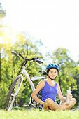 Young female biker with helmet sitting on a grass next to her mountain bike in a park, and relaxing