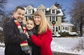 Happy Young Mixed Race Family in Front of Beautiful Snow Covered House.