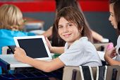 Portrait of schoolboy holding digital tablet while sitting with classmates in classroom