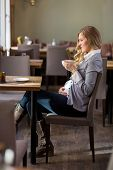Side view of pregnant woman having coffee at table