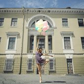 Attractive teen girl dancing with balloons outdoor against old building. Toned
