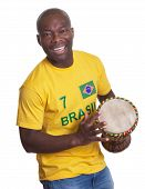 image of samba  - Laughing guy from Brazil with drum loves samba on an isolated white background for cutout - JPG