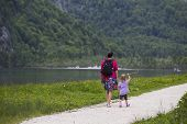 Women And Child Walks Along The Lake