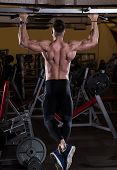 Muscular Young Man Doing Pull Ups (Chin-Ups) in the Gym.