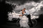 Bride and groom kissing on a bicycle