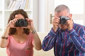 Mature couple at home taking pictures with old analog SLR cameras
