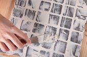 stock photo of grout  - picture of a worker applies grout at grey tiles - JPG