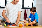 happy dad and son making healthy food together in kitchen