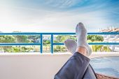 foto of stocking-foot  - Resting pair of feet under a blue sky at a holiday resort - JPG
