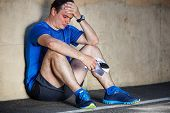 foto of ankle shoes  - Upset Young male runner resting leaning against wall - JPG