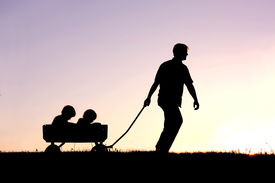 picture of wagon  - The silhouette of a father pulling his two young children behind him in a wagon isolated in front of a sunset in the sky - JPG