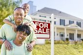 Happy African American Family In Front of For Sale Real Estate Sign and House.