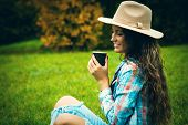 smiling young woman enjoy in coffee break in nature, sit in grass in park, wearing hat, blue torn jeans and tartan shirt