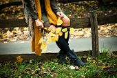 image of woman boots  -  woman sit in park on wooden fence wearing leather boots - JPG