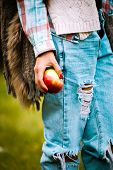 close up of a woman hand hold an apple, wearing blue torn jeans, fur vest and tartan shirt