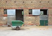Empty Horse Stables With Dirt Wagon On Asphalt