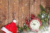 Christmas wooden background with clock, santa hat, snow fir tree and copy space