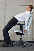 office occupational disease prevention -business man exercising on chair  - profile view