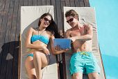 Young couple resting on sun loungers while using digital tablet by swimming pool