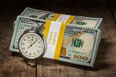 Time is money loan concept background - stopwatch and stack of new 100 US dollars 2013 edition banknotes (bills) bundles on wooden background