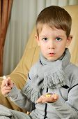 Boy Holding A Thermometer And Pills Vertical