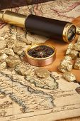 Gold nuggets and vintage brass telescope on antique map