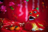 Chinese new year decorations, miniature dancing lion, blossom flower and mandarin orange on red glitter background.