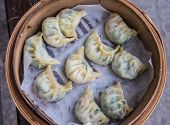 stock photo of steam  - shanghai dumplings with spinach steamed in bamboo basket - JPG