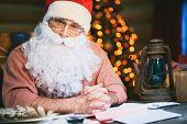 Senior man in Santa cap and beard looking at camera
