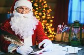 image of letters to santa claus  - Santa Claus answering Christmas letter and looking at camera - JPG