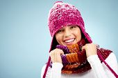 Girl in crimson knitted winter cap and scarf looking at camera with smile