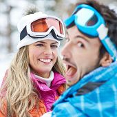 Smiling couple having fun in a ski trip holiday in the snow