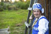 Old woman in Slavic clothing outdoors. Picture with space for text.